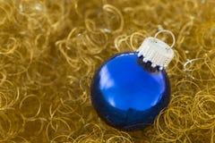 Bola azul de la Navidad en brillo del oro Imagenes de archivo