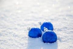 Bola azul de la Navidad en la nieve en un día soleado Fotografía de archivo libre de regalías