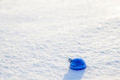 Bola azul de la Navidad en la nieve en un día soleado Fotografía de archivo