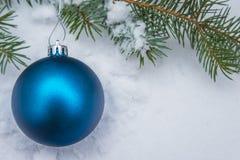 Bola azul de la Navidad en nieve al aire libre Imágenes de archivo libres de regalías