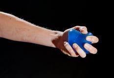 Bola azul de la tensión en una mano femenina Imágenes de archivo libres de regalías
