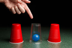 Bola azul debajo de la taza clara con la mano Fotos de archivo