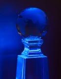 Bola azul del mundo en una base de cristal Imagen de archivo libre de regalías