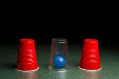 Bola azul ocultada debajo de la taza clara Imagen de archivo libre de regalías