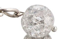 Bola blanca transparente en grietas en una cadena áspera con un beautif Imágenes de archivo libres de regalías