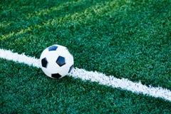 Bola blanco y negro clásica del fútbol en la hierba verde del campo Partido de fútbol, entrenamiento, concepto de la afición foto de archivo libre de regalías