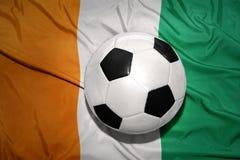 Bola blanco y negro del fútbol en la bandera nacional del divoi del corral Fotos de archivo