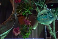 Bola branca de vidro com teste padrão em uma corda contra uma parede na noite Fotografia de Stock Royalty Free