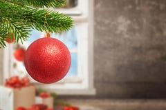 Bola brilhante vermelha do Natal na árvore Presentes, decorações, parede e janela no fundo com espaço da cópia imagens de stock