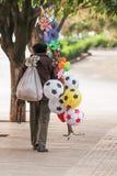 Bola china del vendedor del vendedor ambulante del viejo hombre y otros juguetes en imagen de archivo libre de regalías
