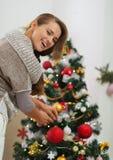 Bola colgante de la Navidad de la mujer en el árbol de navidad Fotografía de archivo libre de regalías