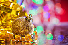 Bola coloreada oro de la Navidad con malla y la cinta en surfa del espejo imagen de archivo