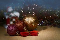 Bola colorida de la Navidad tres en el fondo del luz de una vela-muñeco de nieve de la Navidad y del fondo borroso Imágenes de archivo libres de regalías