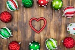 Bola colorida de lujo de la Navidad en el fondo de madera, forma del corazón Fotos de archivo libres de regalías