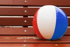 A bola colorida inflável encontra-se em um banco velho Imagem de Stock