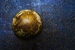 Bola concreta dourada no asfalto escuro molhado imagem de stock royalty free
