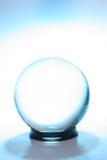 Bola cristalina rodeada por azul Imágenes de archivo libres de regalías