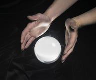 Bola de cristal y manos alrededor Imagenes de archivo