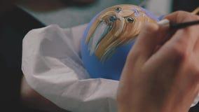 Bola da decoração do ano novo Pintura fêmea na bola do ano novo Bola pintado à mão do ano novo, retrato do cão na bola, lento vídeos de arquivo