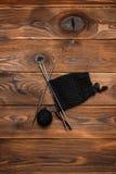 Bola da linha de confecção de malhas preta e do teste padrão de confecção de malhas em um fundo de madeira fotografia de stock