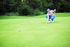 Bola da marcação do jogador de golfe no verde de colocação Imagens de Stock Royalty Free