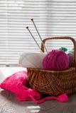 A bola de agulhas do fio e de confecção de malhas na cesta em uma tabela cinzenta de madeira com janela ilumina-se Fim acima hand Fotos de Stock Royalty Free