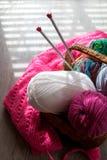 A bola de agulhas do fio e de confecção de malhas na cesta em uma tabela cinzenta de madeira com janela ilumina-se Fim acima Vist Fotografia de Stock Royalty Free
