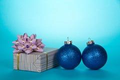 Bola de brilho do Natal dois, presente em papel listrado com uma curva bonita grande no azul Fotos de Stock Royalty Free