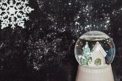 Bola de cristal con el copo de nieve en fondo oscuro Imagen de archivo