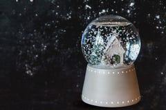 Bola de cristal con el copo de nieve en fondo oscuro Fotos de archivo
