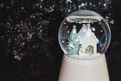Bola de cristal con el copo de nieve en fondo oscuro Imágenes de archivo libres de regalías