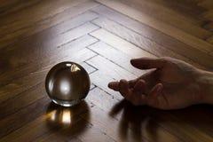 Bola de cristal con la mano Foto de archivo