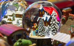 Bola de cristal con las figuras y adorno de la Navidad Imagenes de archivo