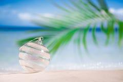Bola de cristal de la Navidad en la playa con el fondo del paisaje marino Imagenes de archivo