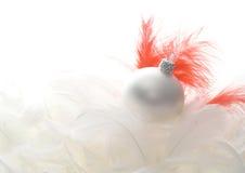 Bola de cristal de la Navidad en plumas Imágenes de archivo libres de regalías