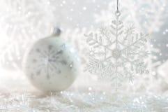 Bola de cristal de la Navidad con los copos de nieve en un fondo blanco con el bokeh Foco selectivo Fotos de archivo