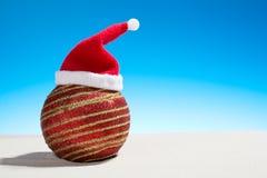 Bola de cristal de la Navidad que lleva un sombrero de Papá Noel en la playa Imagen de archivo libre de regalías
