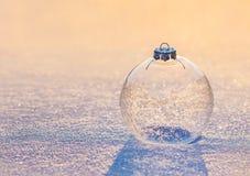 Bola de cristal transparente de la Navidad con los copos de nieve en nieve de la puesta del sol Fotos de archivo libres de regalías