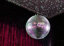 Bola de discoteca brillante en fondo rojo Foto de archivo