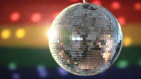 Bola de discoteca que gira contra bandera del orgullo gay metrajes