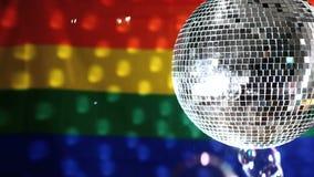 Bola de discoteca que gira contra bandera del orgullo gay almacen de metraje de vídeo