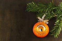 Bola de espejo anaranjada grande en el árbol de Navidad, fondo negro Imágenes de archivo libres de regalías