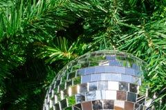 Bola de espejo en el árbol de navidad con la reflexión de la chispa Imágenes de archivo libres de regalías