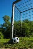 A bola de futebol é ao lado do polo de um objetivo com correntes, futebol para crianças imagem de stock