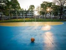 Bola de futebol amarela velha no campo de futebol azul fotos de stock