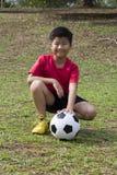 Bola de futebol da pose da jovem criança no campo de grama verde Fotos de Stock