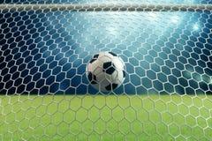 bola de futebol da rendição 3d no objetivo Bola de futebol na rede com fundo claro do projetor e do estádio, conceito do sucesso Imagem de Stock Royalty Free
