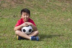 Bola de futebol do pontapé da jovem criança no campo de grama verde Fotografia de Stock