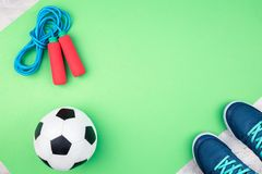 Bola de futebol e corda de salto na esteira verde imagens de stock royalty free
