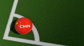 Bola de futebol em cores nacionais de China em um campo de futebol Copie o espaço no lado direito Imagens de Stock Royalty Free